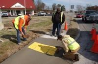 Three men working on a sidewalk project.