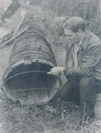 In this 1960's photograph, Don Bledsoe examines a section of the 1919 wooden stave pipe.