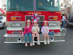 Three children sitting on the front of a fire truck.