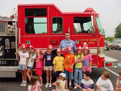 A firefighter standing in front of a fire truck with a group of kids.
