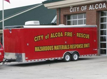 "A large red trailer with words on the side, ""City of Alcoa Fire-Rescue, Hazardous Materials Respo"