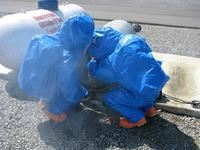 Two people in blue plastic suits handling hazardous materials.