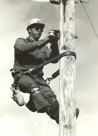 Black and white photo of an electrical working on high on a pole.