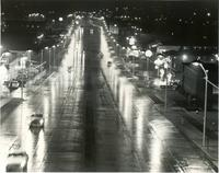 A black and white photo of a lighted freeway at night.