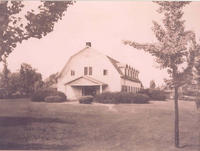 A black and white photo of a white barn house.