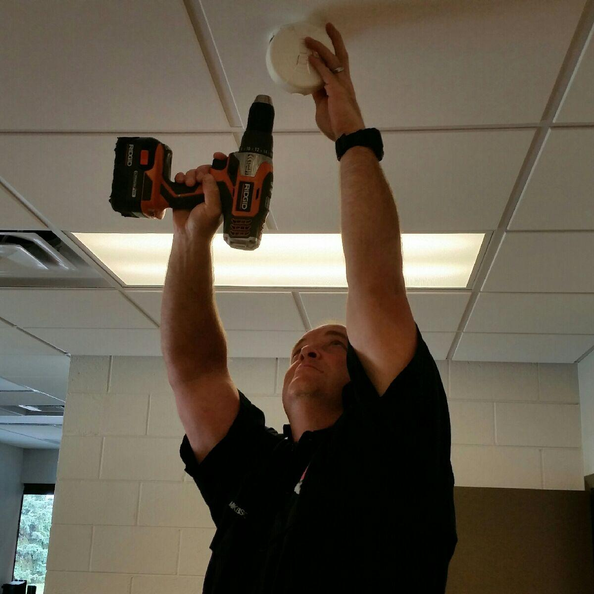 Mike Harrison installing a smoke detector