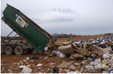 A dump truck dumping its load onto a pile.