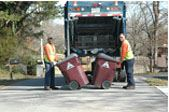 Two workers loading trash onto a truck.
