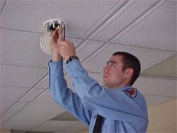A firefighter installing a smoke detector.